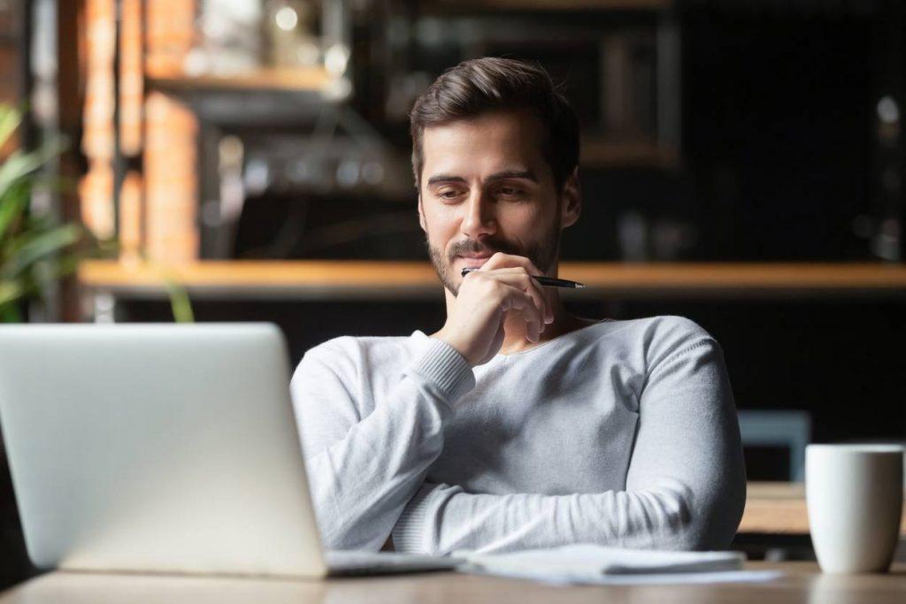 Un homme réfléchit devant son ordinateur